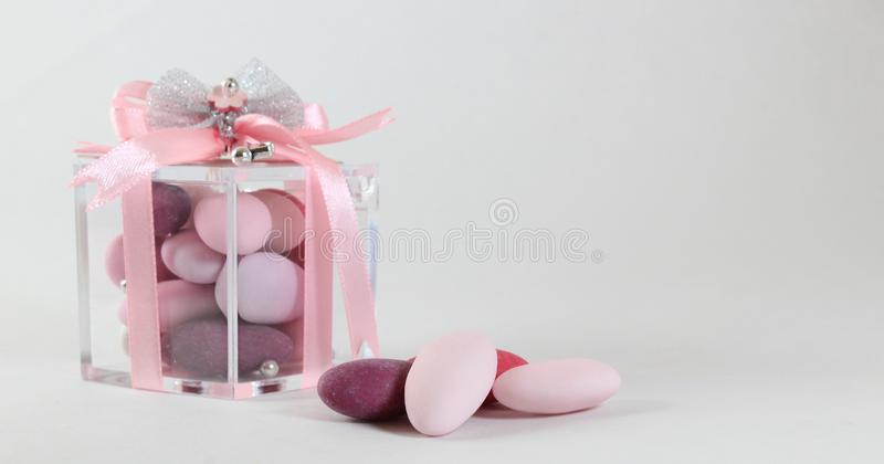 Background for baby girl baptism with pink sugared almonds stock photography