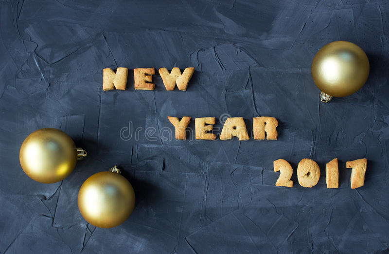 Background with baked gingerbread words happy new year 2017 and christmas balls. creative idea royalty free stock photography