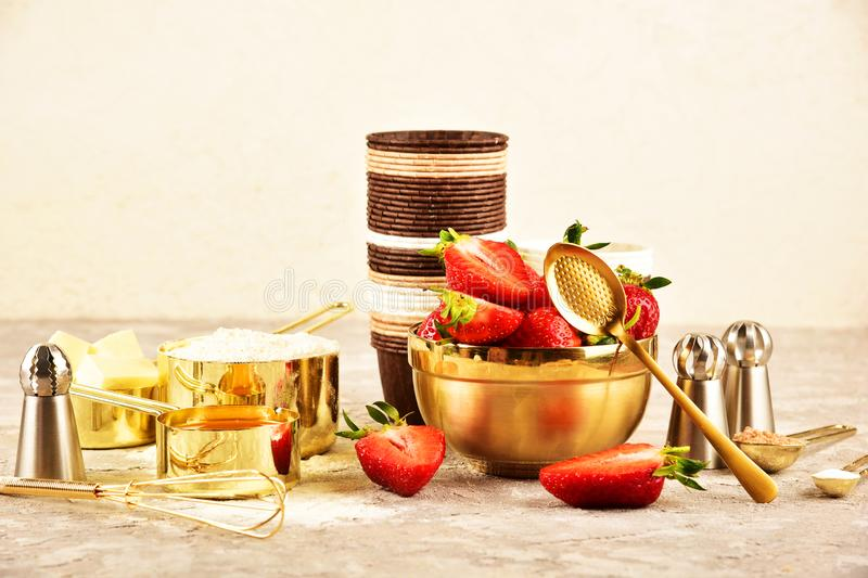 Background baking flat lay with golden devices, strawberries and flour. Background baking flat lay with golden devices, strawberries and flour royalty free stock photography