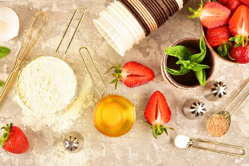 Background baking flat lay with golden devices, strawberries and flour. Background baking flat lay with golden devices, strawberries and flour royalty free stock image
