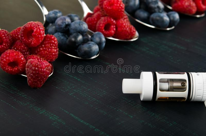 Background of berries in spoons of raspberries and blueberries, next to an electronic cigarette on a black background stock images