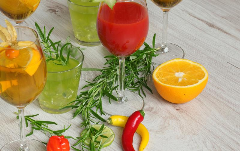 Background with beverages - colorful coctails, orange, chilli pepper and rosemay together royalty free stock photo