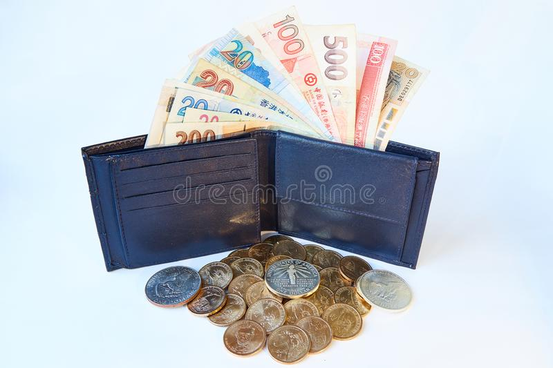 Background, black men`s wallet with bills of various currencies and yellow metal dollars, isolated royalty free stock photo