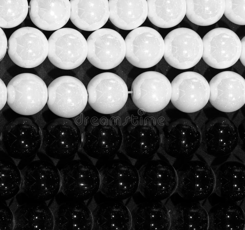 Background of black and white pearls. Symbol of positive and negative royalty free stock photography