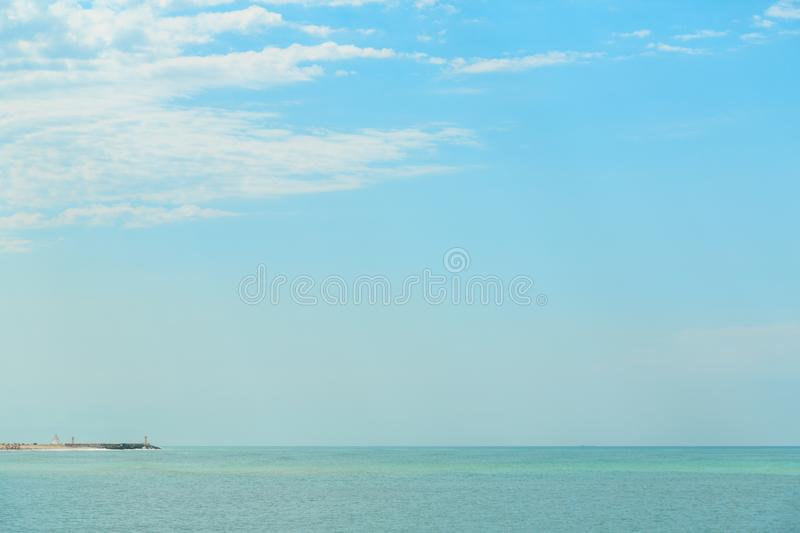 Background of blue sky with beautiful clouds and a small part of the azure sea in the frame. the focus is selective.  royalty free stock photography
