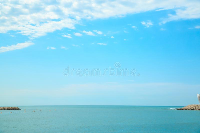 Background of blue sky with beautiful clouds and a small part of the azure sea in the frame. the focus is selective.  royalty free stock images