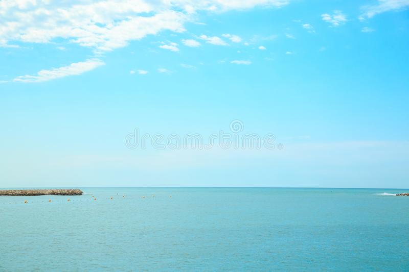 Background of blue sky with beautiful clouds and a small part of the azure sea in the frame. the focus is selective.  royalty free stock photos