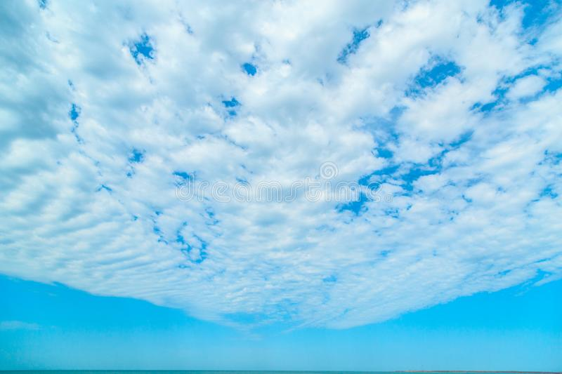 Background of blue sky with beautiful clouds and a small part of the azure sea in the frame. the focus is selective.  stock photos