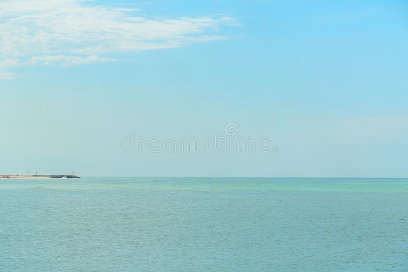 Background of blue sky with beautiful clouds and a small part of the azure sea in the frame. the focus is selective.  stock photography