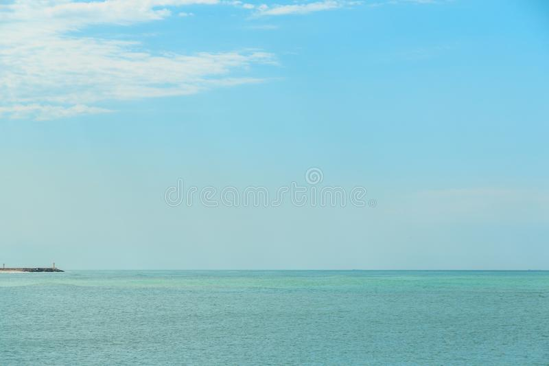 Background of blue sky with beautiful clouds and a small part of the azure sea in the frame. the focus is selective.  stock image
