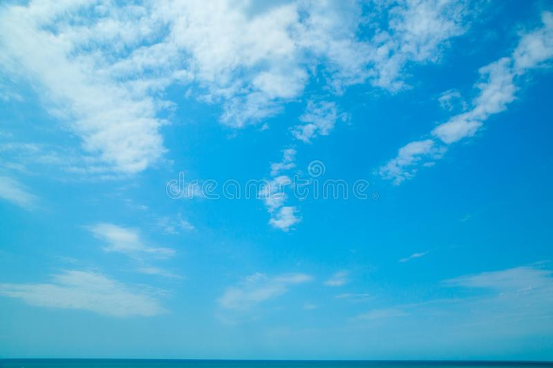 Background of blue sky with beautiful clouds and a small part of the azure sea in the frame. the focus is selective.  royalty free stock image