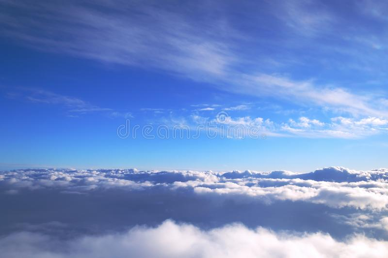 Background of blue sky over cumulus clouds with the rays of the setting sun. stock photography