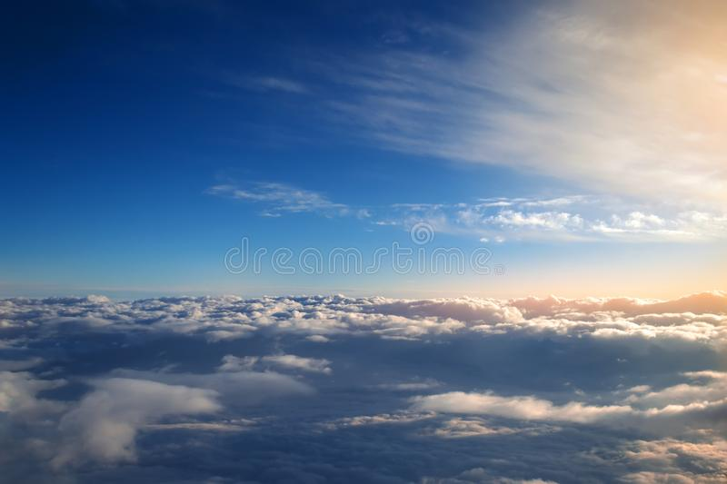 Background of blue sky over cumulus clouds with the rays of the setting sun. royalty free stock photography