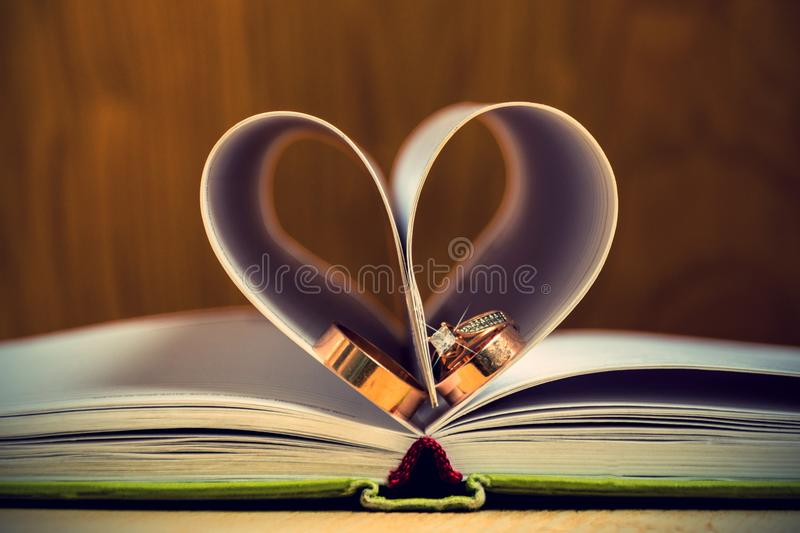 Wedding rinds paper heart made with book`s pages. Background blur book composition empty happy heart love open pages paper rings wedding romance romantic shape stock image