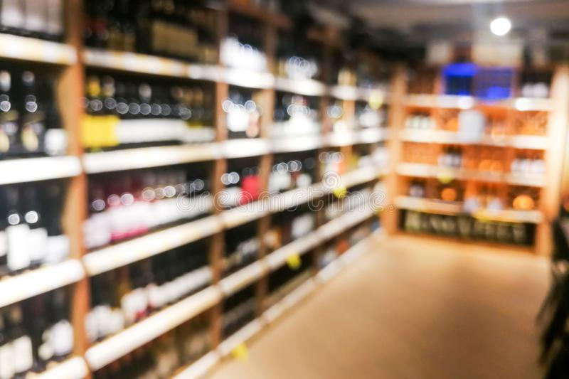 Background blur of wine shelf rack at retail store. Background blur of wine shelf rack at retail supermarket store, alcohol, bar, beverage, blurred, bokeh royalty free stock photos