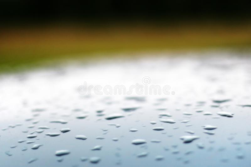 Background with blurred drops on the roof of a silver blue car and a green backdrop. stock photos