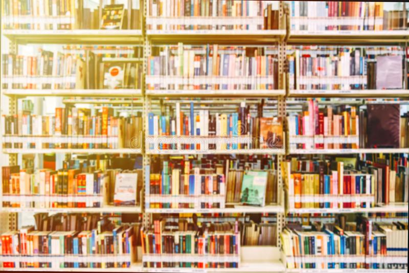The background blurred Image many books on bookshelf in library and orange leak light.  royalty free stock photography