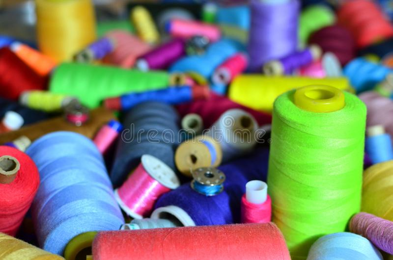 Background of bobbins with multicolored threads for sewing. Needlework, sewing and tailoring concept. royalty free stock photos