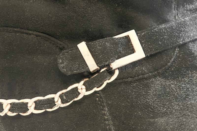 Background bootleg of a leather boot with a yellow buckle and chain stock image