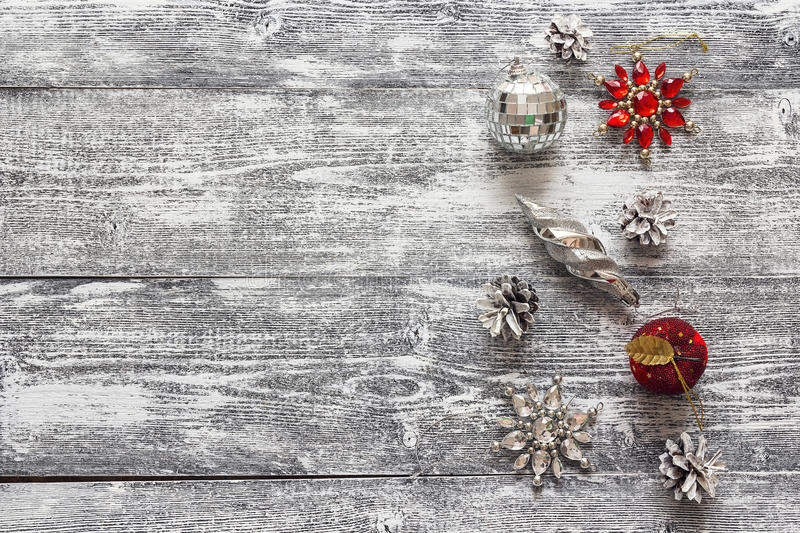 Background with a border of Christmas decorations and white pai. Nted pine cones on gray wooden table. Space for text. Top view royalty free stock photography