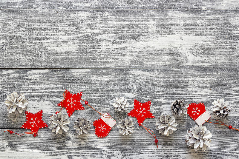 Background with a border of red Christmas decorations and white. Painted pine cones on gray wooden table. Space for text. Top view stock photography