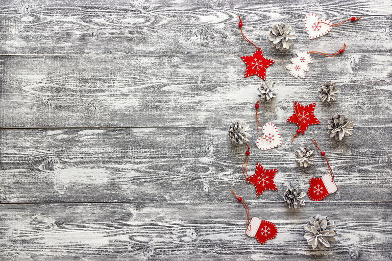 Background with a border of red Christmas decorations and white. Painted pine cones on gray wooden table. Space for text. Top view royalty free stock images