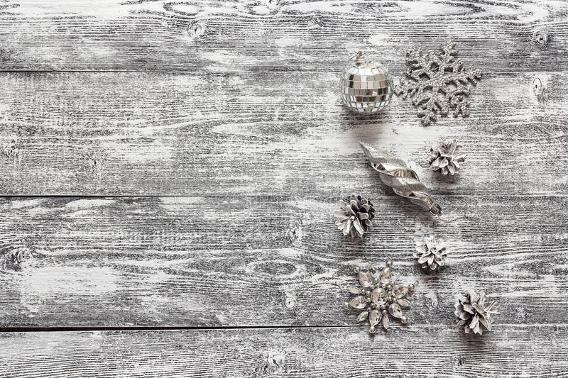 Background with a border of silver Christmas decorations and white painted pine cones on gray wooden table. Space for text. Top view royalty free stock photography