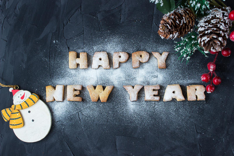 Background with branch of christmas tree, snowmen and baked gingerbread words happy new year with powdered sugar stock photos