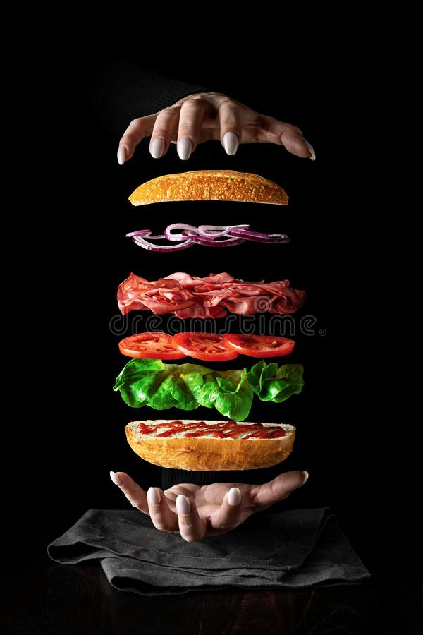Food levitation. sandwich. Background bread delicious cheese, salad, tomatoes breakfast brown, food calories close diet levitation process hands chef salad stock image
