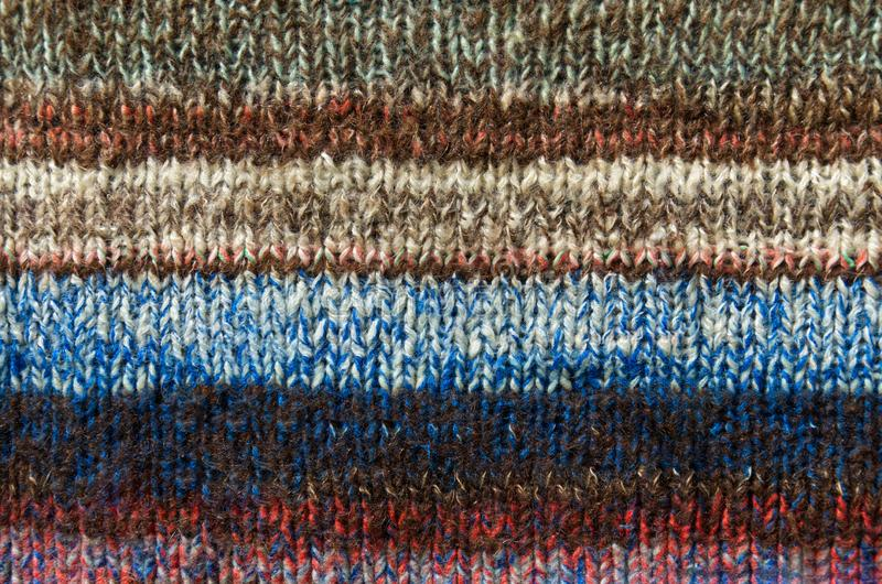 Bright multi color striped fabric knitted by the hand stock photo