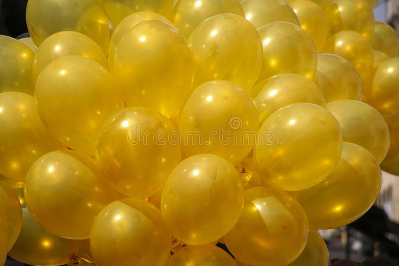 Background of bright yellow inflatable balloons up in the air, b stock image