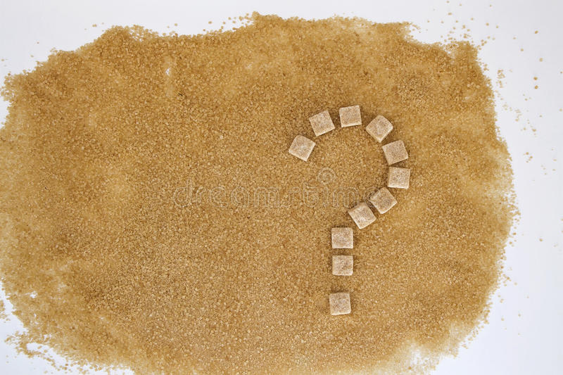 Background of brown sugar cubes shaped as a question mark. Top view. Diet unhealty sweet addiction concept. The question mark of brown sugar cubes on cystal royalty free stock photography