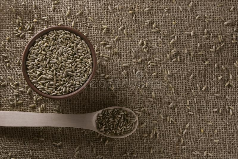 Background from burlap with filled with rye grain a clay bowl and a wooden spoon. stock photos