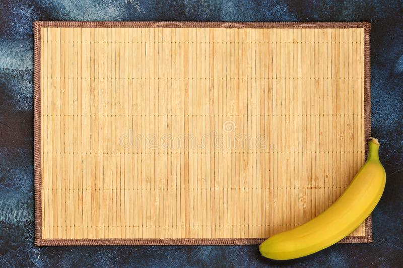 Background with cane backing and a ripe yellow banana. On a dark blue background - the view from the top, flat layer, copyspace stock photography