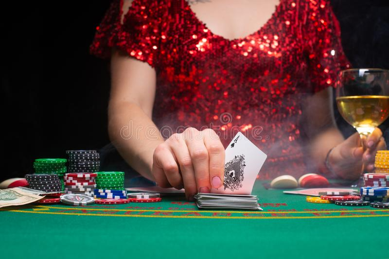 BACKGROUND FOR CASINO. A girl in an evening red dress plays in a casino, holds an ace card. Gambling business casino.  royalty free stock photo