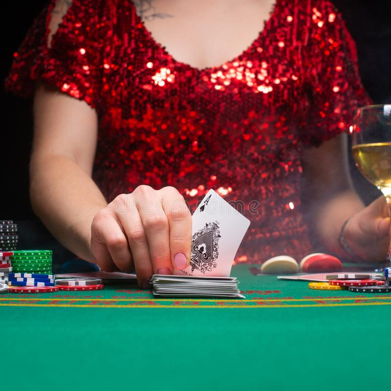 BACKGROUND FOR CASINO. A girl in an evening red dress plays in a casino, holds an ace card. Gambling business casino.  royalty free stock image