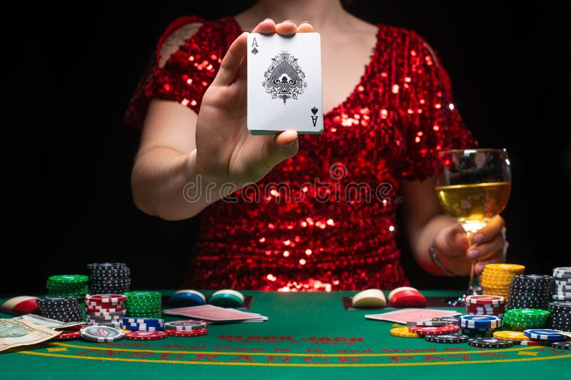 BACKGROUND FOR CASINO. A girl in an evening red dress plays in a casino, holds an ace card. Gambling business casino.  stock photography