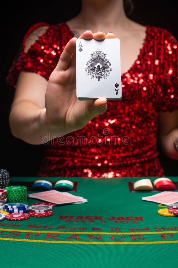 BACKGROUND FOR CASINO. A girl in an evening red dress plays in a casino, holds an ace card. Gambling business casino.  stock photos