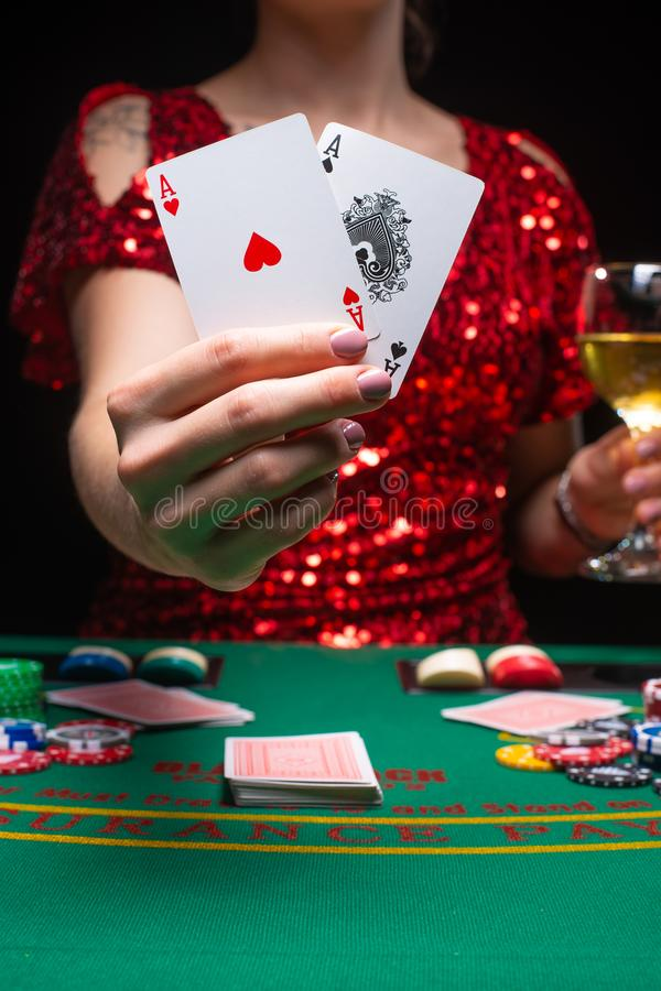 BACKGROUND FOR CASINO. A girl in an evening red dress plays in a casino, holds aces cards. Gambling business casino.  royalty free stock photography