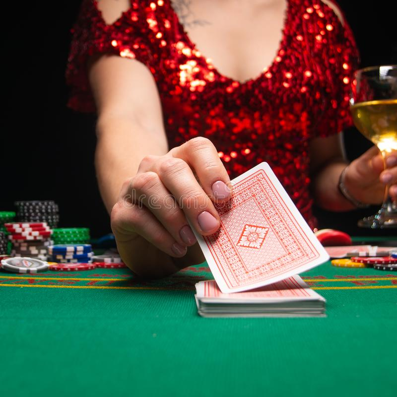 BACKGROUND FOR CASINO. A girl in an evening red dress plays in a casino, holds cards. Gambling business casino.  royalty free stock photos