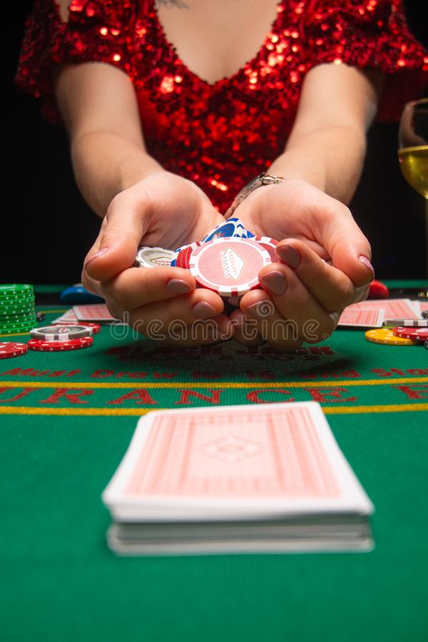 BACKGROUND FOR CASINO. A girl in an evening red dress plays in a casino, holds cards. Gambling business casino.  stock images