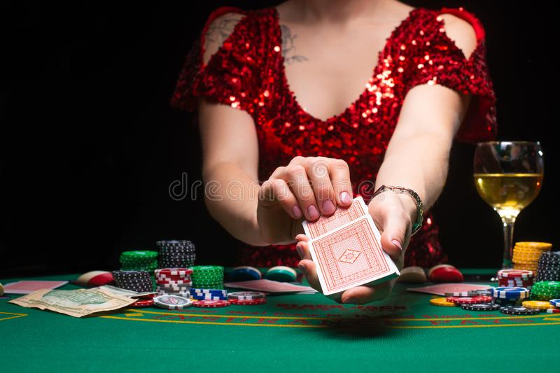 BACKGROUND FOR CASINO. A girl in an evening red dress plays in a casino, holds cards. Gambling business casino.  stock photo