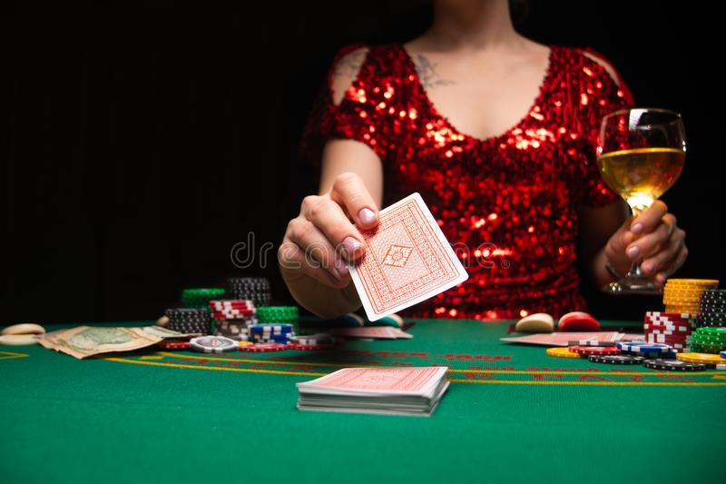 BACKGROUND FOR CASINO. A girl in an evening red dress plays in a casino, holds moles. Gambling business casino.  stock photo