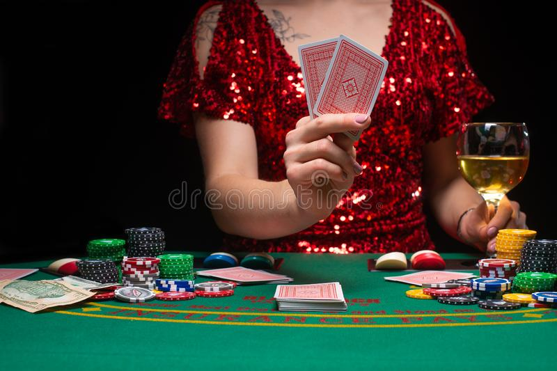 BACKGROUND FOR CASINO. A girl in an evening red dress plays in a casino, holds moles. Gambling business casino.  royalty free stock photos