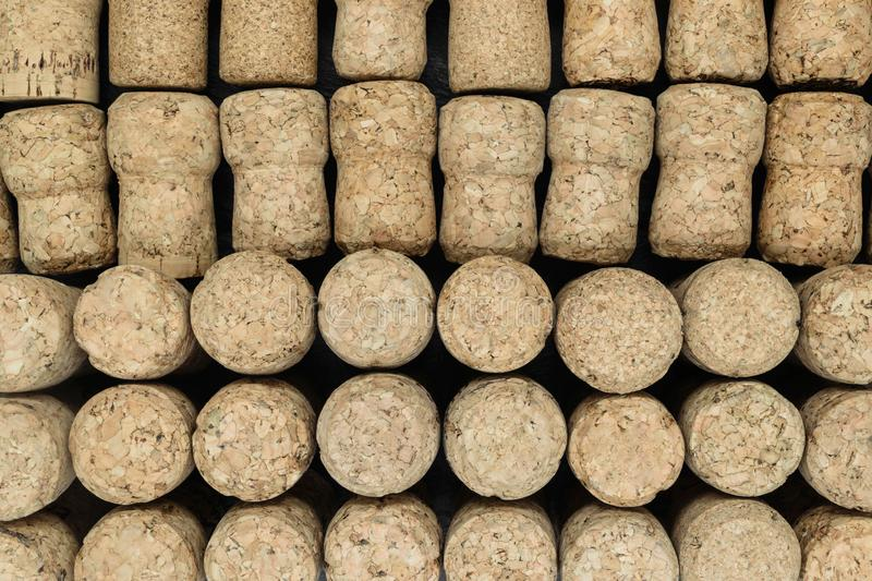 Background of champagne corks. Half of corks lying, half of them standing on black stone background royalty free stock images