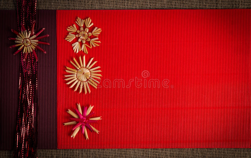 Background for Christmas greeting card- holiday straw decoration, red and claret textured paper. Background for Christmas greeting card. Composition of christmas stock image