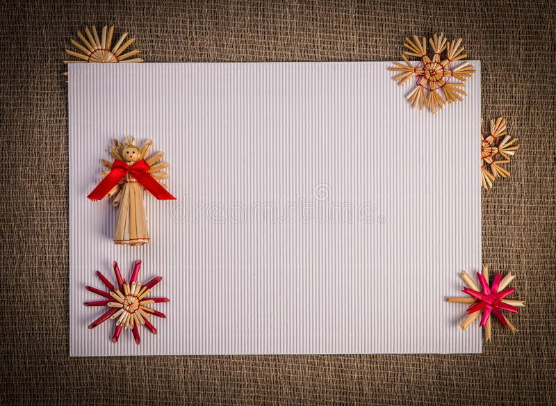 Background for Christmas greeting card- holiday straw decoration, red and claret textured paper. Background for Christmas greeting card. Composition of christmas royalty free stock photos