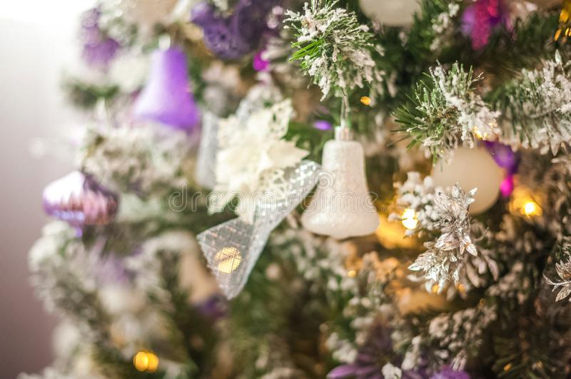 Background from a Christmas tree decorated in blue and purple close-up. Greeting card from a Christmas tree with purple decoration stock photo