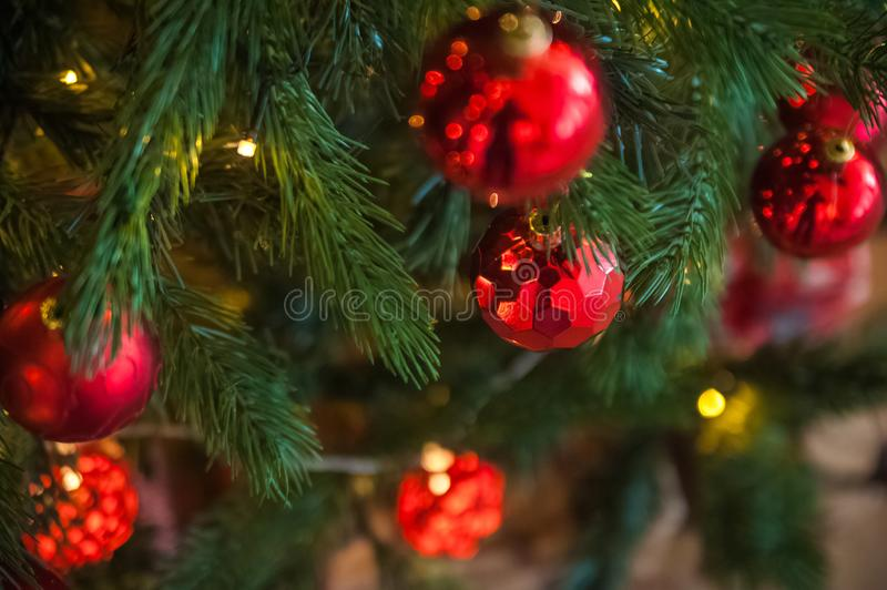 Background from a Christmas tree decorated in red and gold color close-up. Greeting card from a Christmas tree with red decoration royalty free stock image