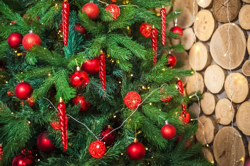 Background from a Christmas tree decorated in red and gold color close-up. Greeting card from a Christmas tree with red decoration stock photography